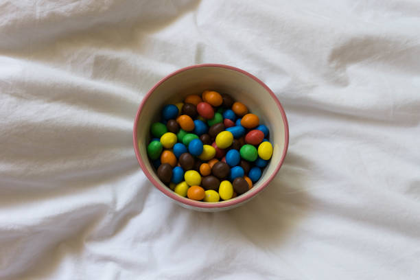 Bowl of M&M's in a bed. Disconnection moment on the bed. Self care concept. Rest and enjoy moment. Detail. stock photo