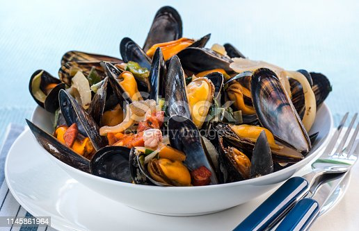 Bowl of cooked mussels  on napkin.