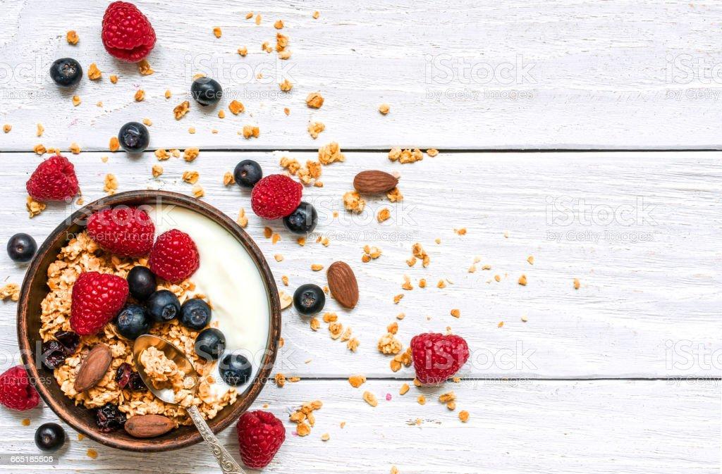 bowl of oat granola with yogurt, fresh raspberries, blueberries and nuts stock photo