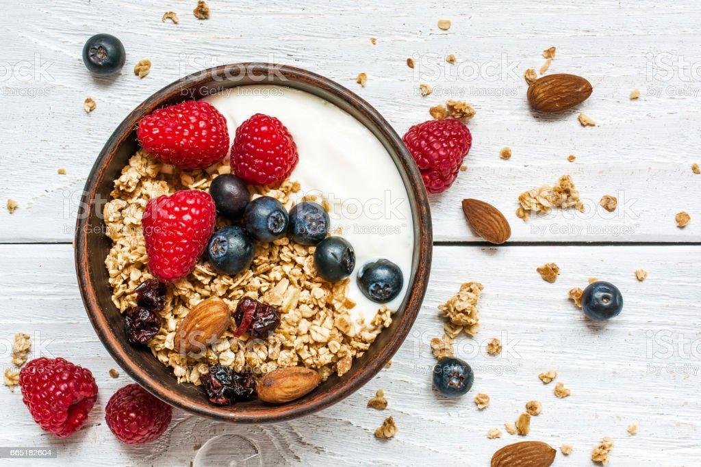 bowl of oat granola with yogurt, fresh raspberries, blueberries stock photo