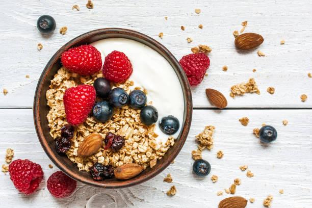 bowl of oat granola with yogurt, fresh raspberries, blueberries - granola imagens e fotografias de stock
