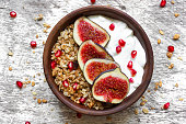 bowl of oat granola with yogurt, pomegranate seeds, figs, grape and nuts with a spoon