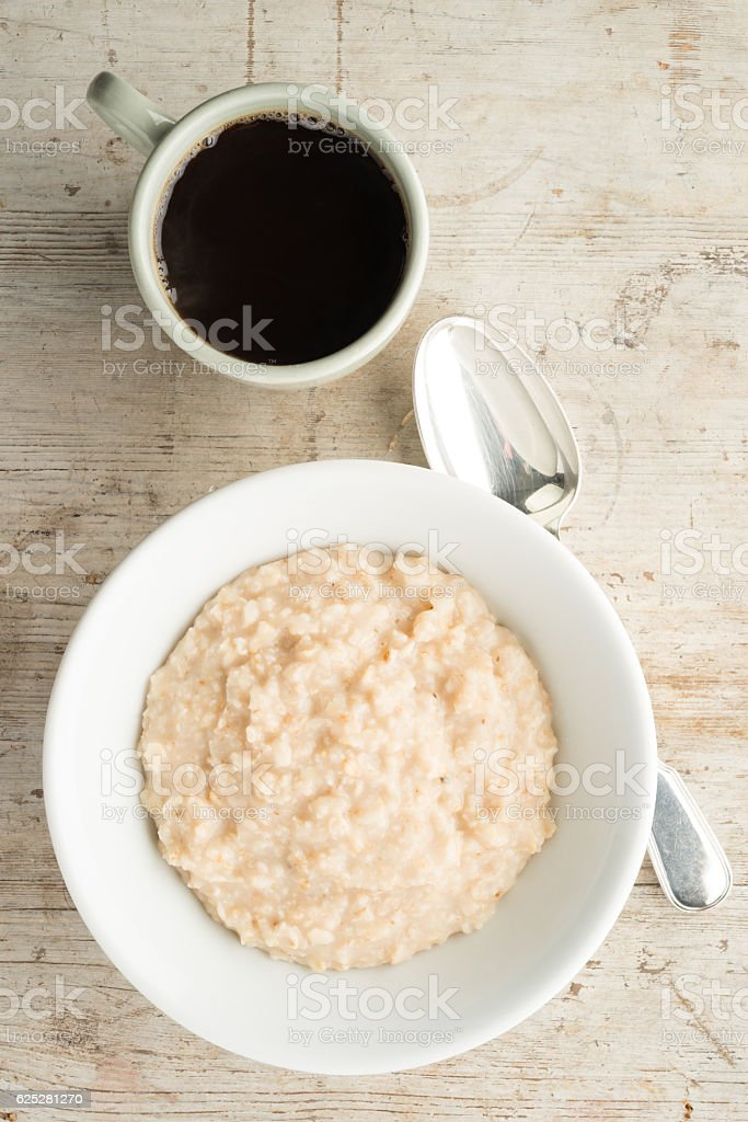 Bowl of Oatmeal and Coffee on Wooden Background stock photo