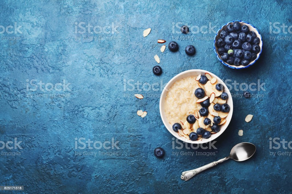 Bowl of oatmeal porridge with banana and blueberry on vintage table top view in flat lay style. Healthy breakfast. stock photo