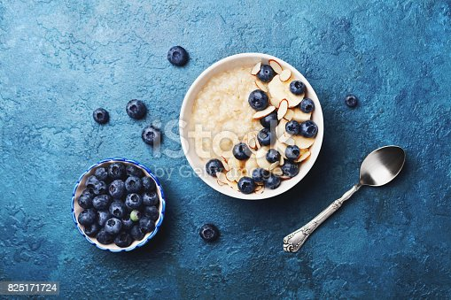 825171518 istock photo Bowl of oatmeal porridge with banana and blueberry on vintage table top view in flat lay style. Homemade breakfast. 825171724