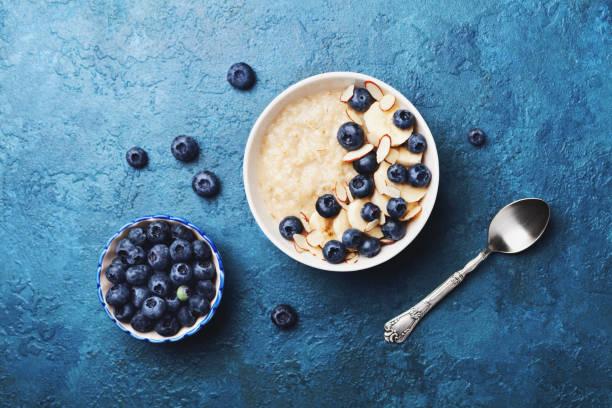 schüssel mit haferflocken-porridge mit banane und heidelbeere in flach legen stil vintage table-top zu sehen. hausgemachtes frühstück. - getreidebrei stock-fotos und bilder