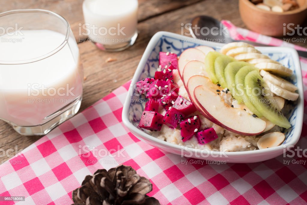 Bowl of oatmeal porridge with bananas, apple, dragon fruit and almonds. Top view royalty-free stock photo