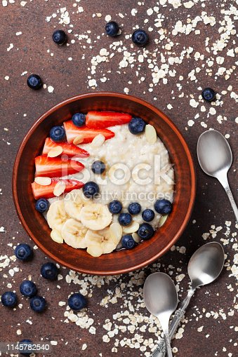 825171518 istock photo Bowl of oatmeal porridge with strawberry, blueberry and banana on kitchen table top view. 1145782540