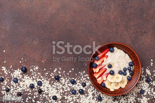 825171518 istock photo Bowl of oatmeal porridge with strawberry, blueberry and banana on brown table top view. Healthy breakfast. 1145783167