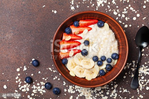 825171518 istock photo Bowl of oatmeal porridge with strawberry, blueberry and banana on table top view. Healthy breakfast. 1145782495