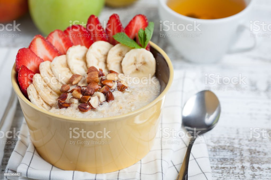 Bowl of oatmeal with a banana, strawberries, almonds, hazelnuts and butter on a rustic table. Hot and a healthy dish for Breakfast, top view foto de stock royalty-free