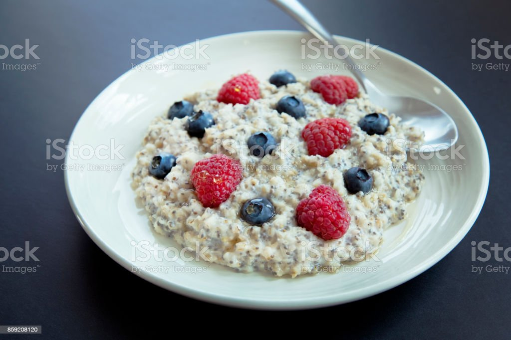 Bowl of oatmeal with  berrias on black background. Breakfast with oatmeal, raspberries, blueberries, chia seeds and honey  in a bowl. Helthy homemade breakfast. Healthy snack or breakfast in the morning. stock photo