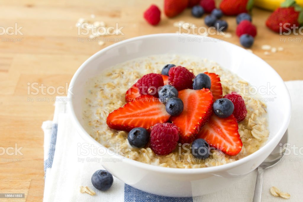 A bowl of oatmeal with blue berries and strawberries stock photo