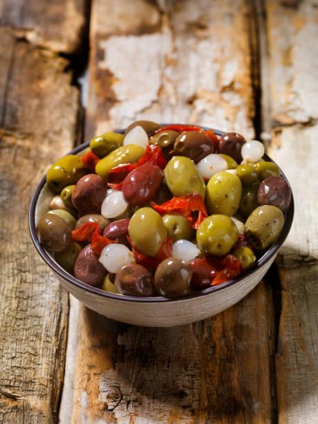 schüssel mit oliven mit zwiebeln und paprika - perlzwiebeln stock-fotos und bilder