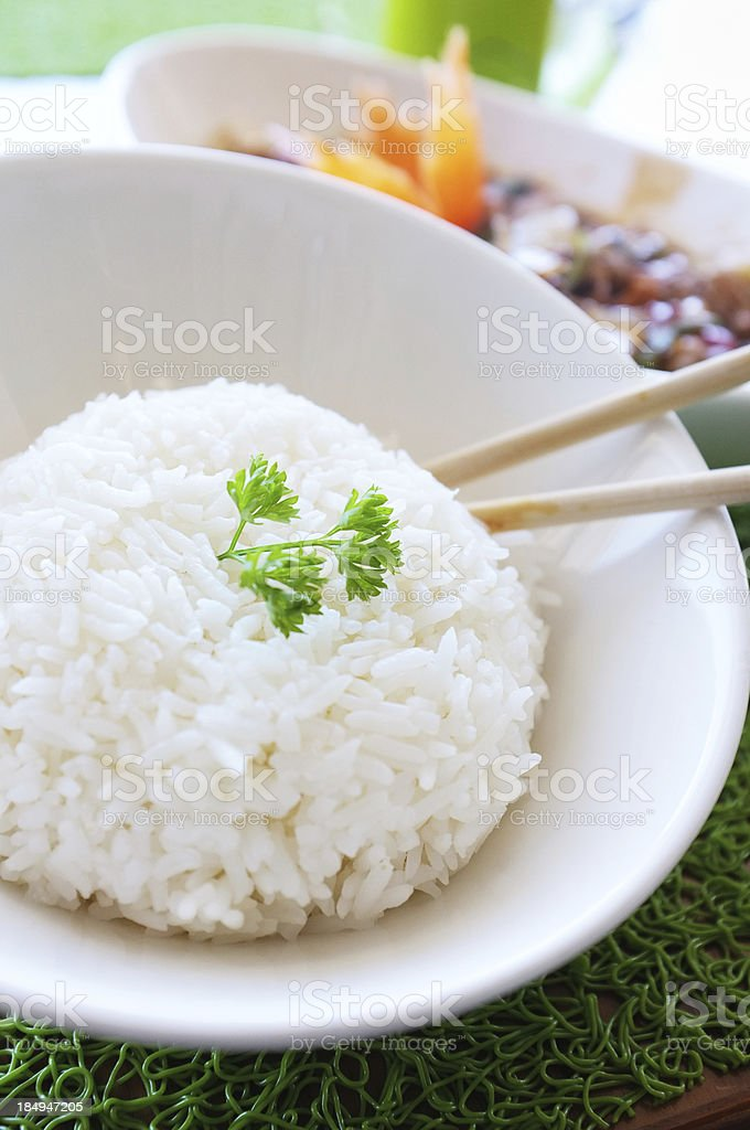 Bowl of oriental jasmine rice with Thai pork dish behind stock photo