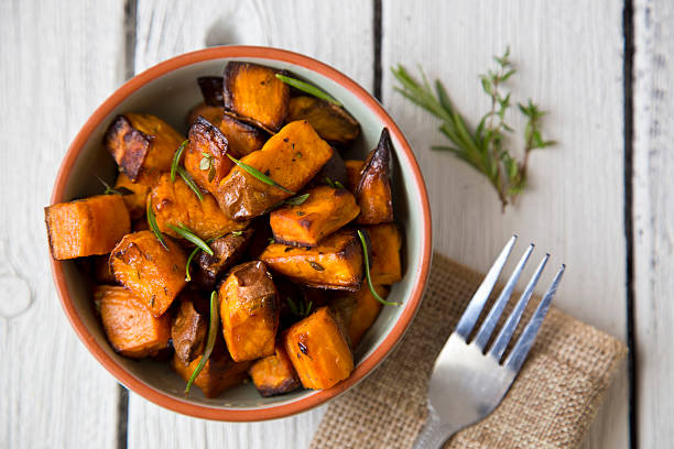 Bowl of oven roasted Sweet Potato with rosemary and thyme stock photo