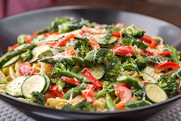 Bowl of Pasta Primavera A large pasta bowl is full of delicious Pasta Primavera made with fresh asparagus, broccoli, red bell pepper and zucchini and is served over a bed of linquine.  One image in a series. primavera stock pictures, royalty-free photos & images