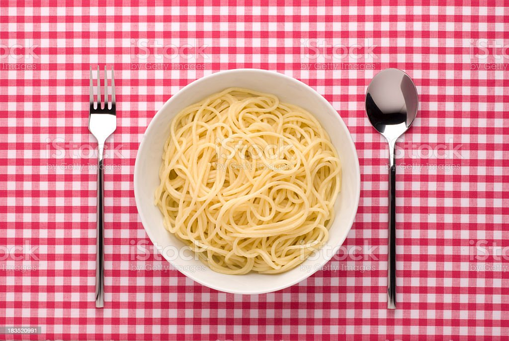 Bowl of pasta with fork and spoon on gingham royalty-free stock photo