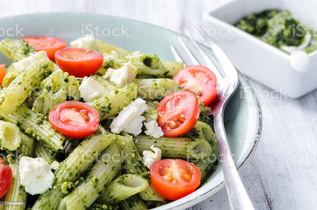 Bowl of pasta with fresh tomatoes and pesto on table stock photo