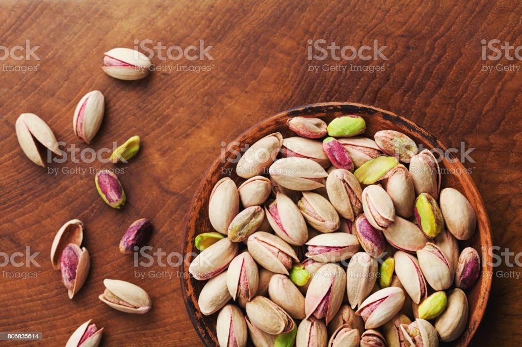 Taza de pistachos sobre vista de madera rústica mesa. Alimentos saludables y aperitivos. Vintage. - foto de stock