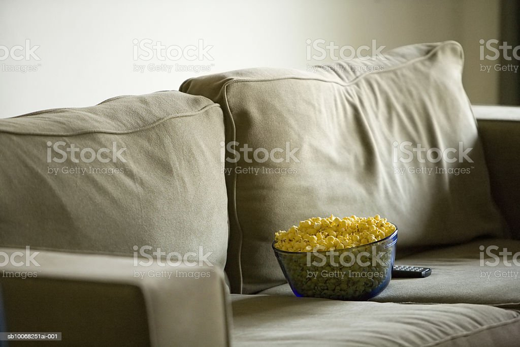 Bowl of popcorn and remote control on sofa royalty-free stock photo