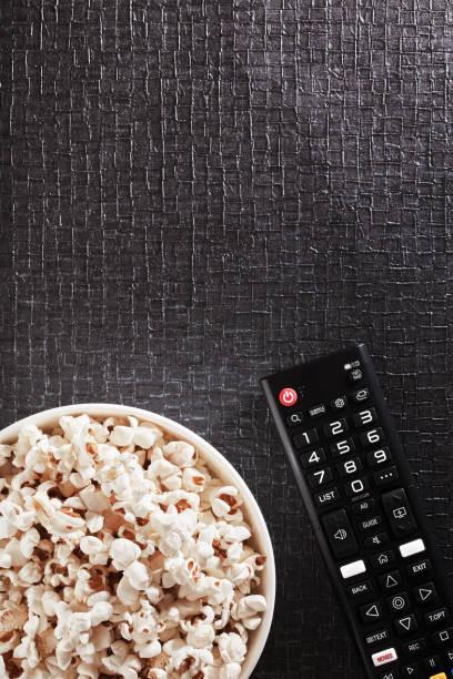bowl of popcorn with tv remote control on a black textured background - telecomando background foto e immagini stock