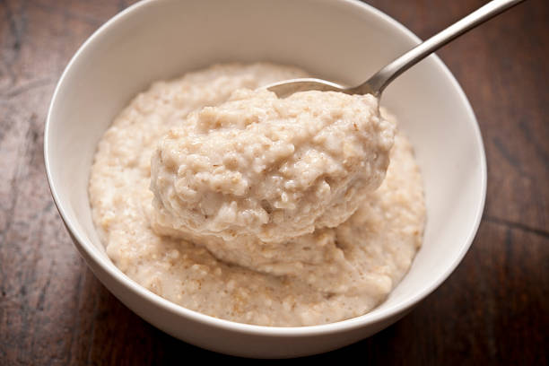 bowl of porridge bowl of Oatmeal ( Porridge ) from above with spoon. porridge stock pictures, royalty-free photos & images
