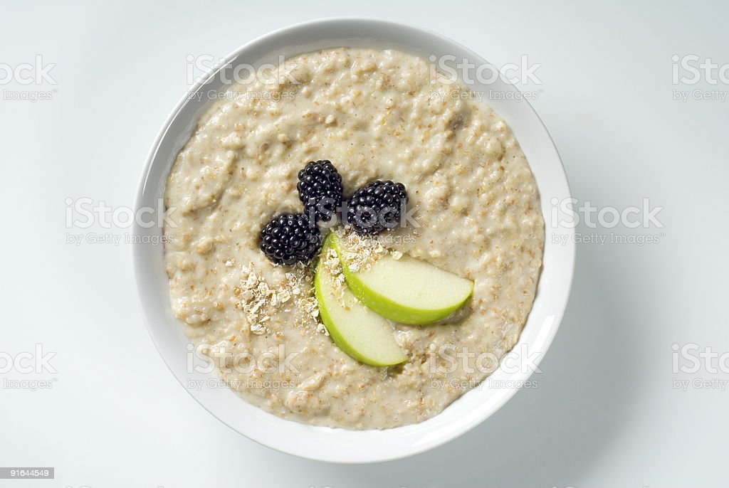 Bowl of porridge with apples and berries stock photo