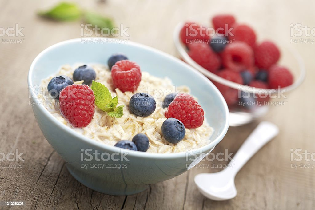 Bowl of porridge with blueberries and raspberries stock photo