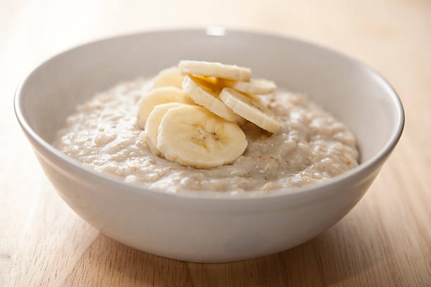 Bowl of porridge with sliced banana Bowl of porridge (oatmeal) with sliced banana. porridge stock pictures, royalty-free photos & images