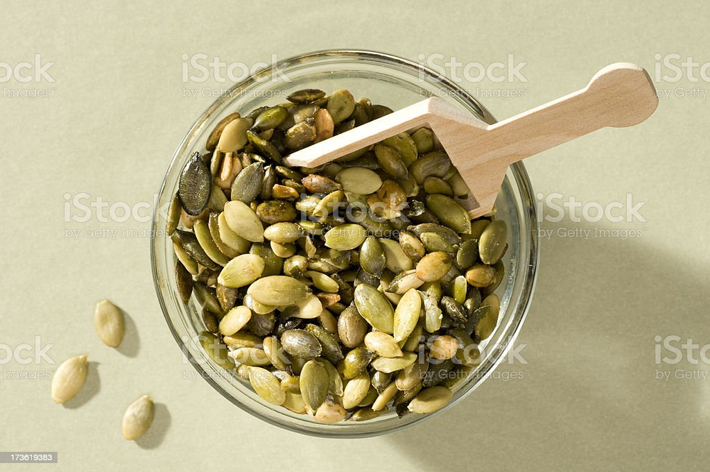 Bowl of Pumpkin Seeds w/wooden scoop-isolated close-up royalty-free stock photo