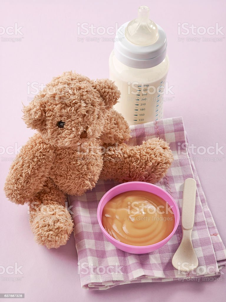 bowl of pureed apple and baby milk bottle foto