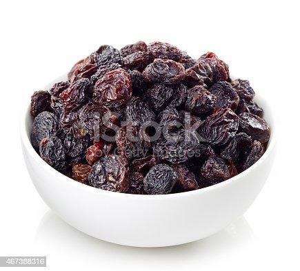 Bowl of dark raisins isolated on white background