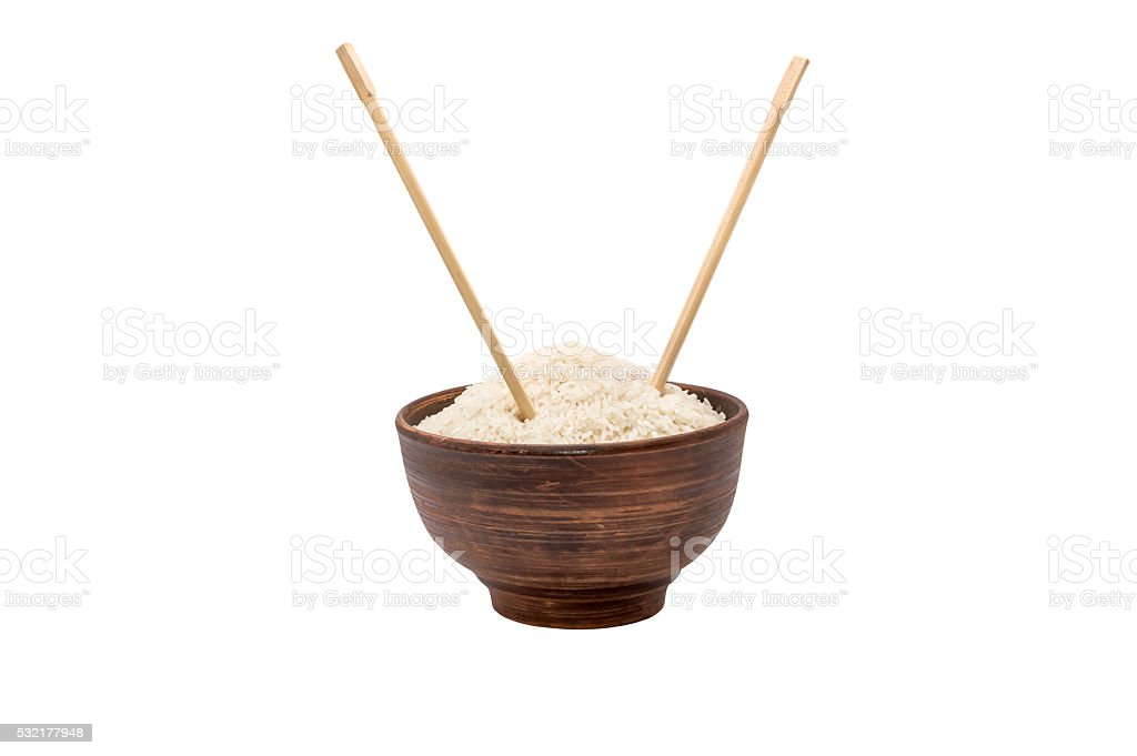Bowl of raw rice with chopsticks isolated on white stock photo