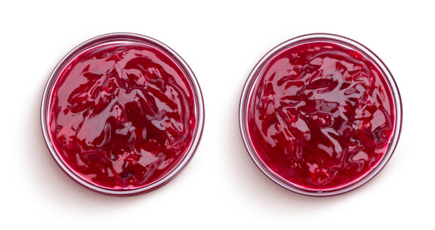 bowl of red berry jam isolated on white background, top view - marmellata foto e immagini stock