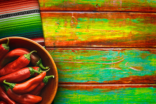 Bowl Of Red Chili Peppers On Vibrant Background Stock Photo - Download Image Now