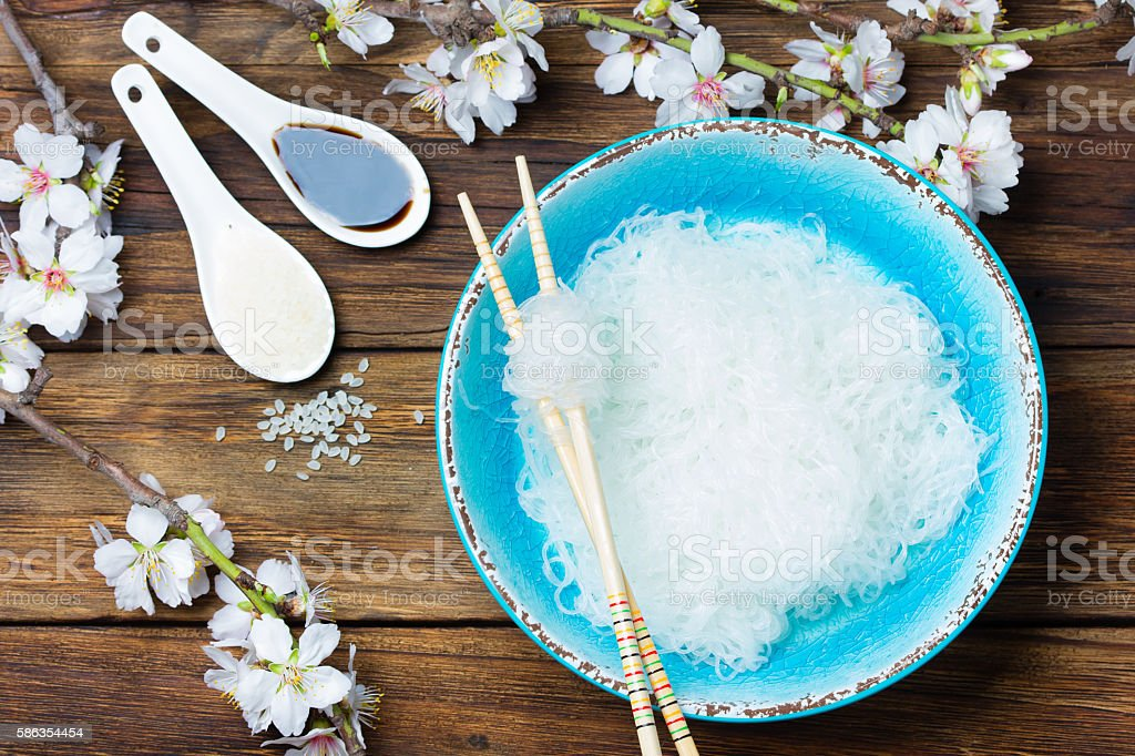 Bowl of rice flat noodles on wooden background stock photo