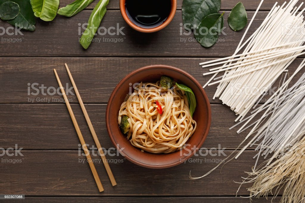 Bowl of rice noodles with soy souce on wooden background stock photo