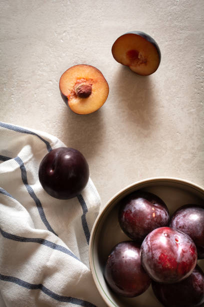 A bowl of ripe plums on a striped napkin and scattered plums on a marble top. Flatlay photo. stock photo