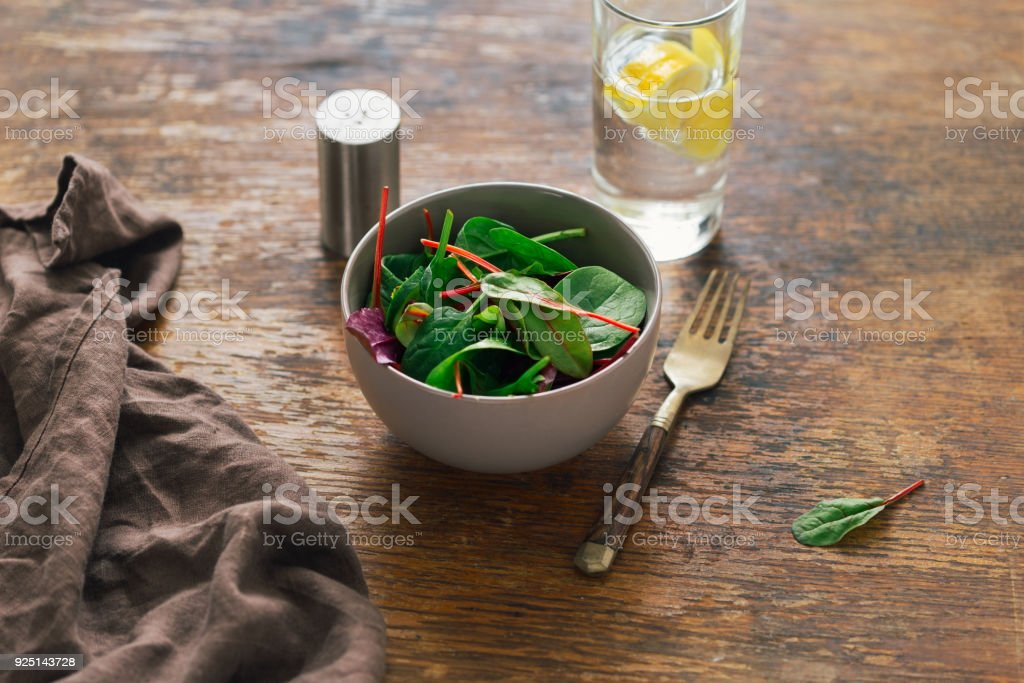 Bowl of salad with spinach leaves and beet leaves on dark wooden table with glass of water with lemon. Vegetarian biodynamic food concept - foto stock