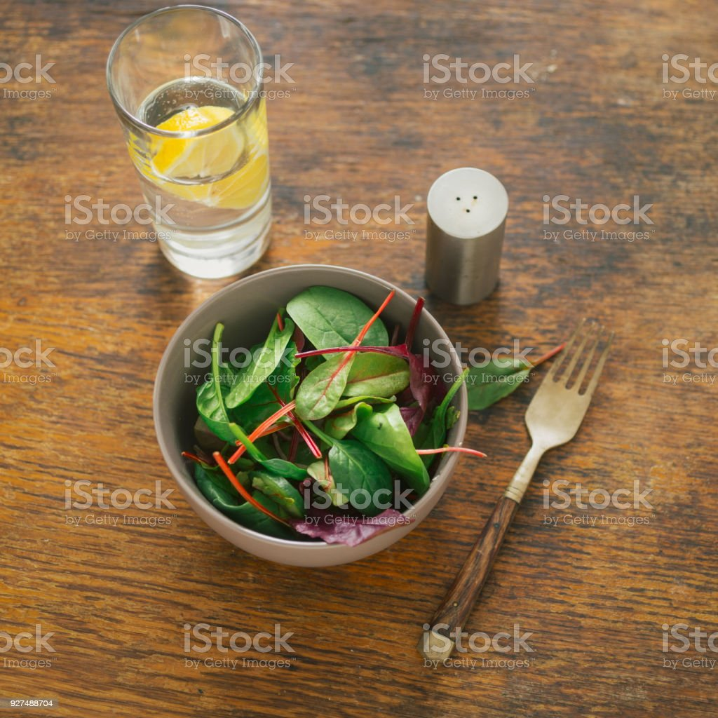 Bowl of salad with spinach leaves and beet leaves on dark wooden table with glass of water with lemon. Top view. Vegetarian biodynamic food concept - foto stock