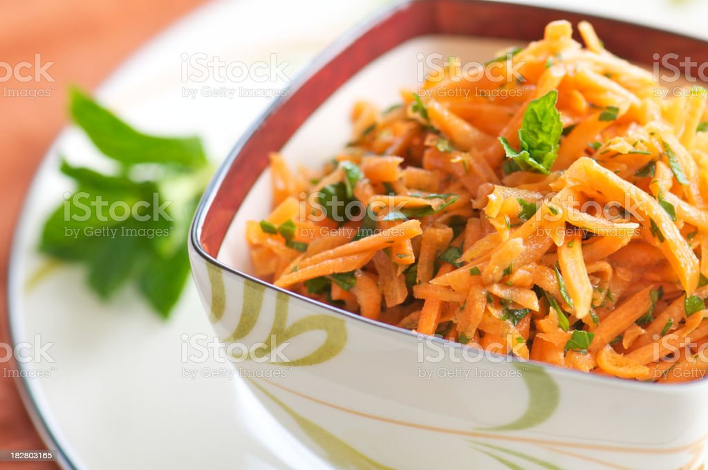 Bowl of Shredded Carrot Salad with Chopped Herbs stock photo