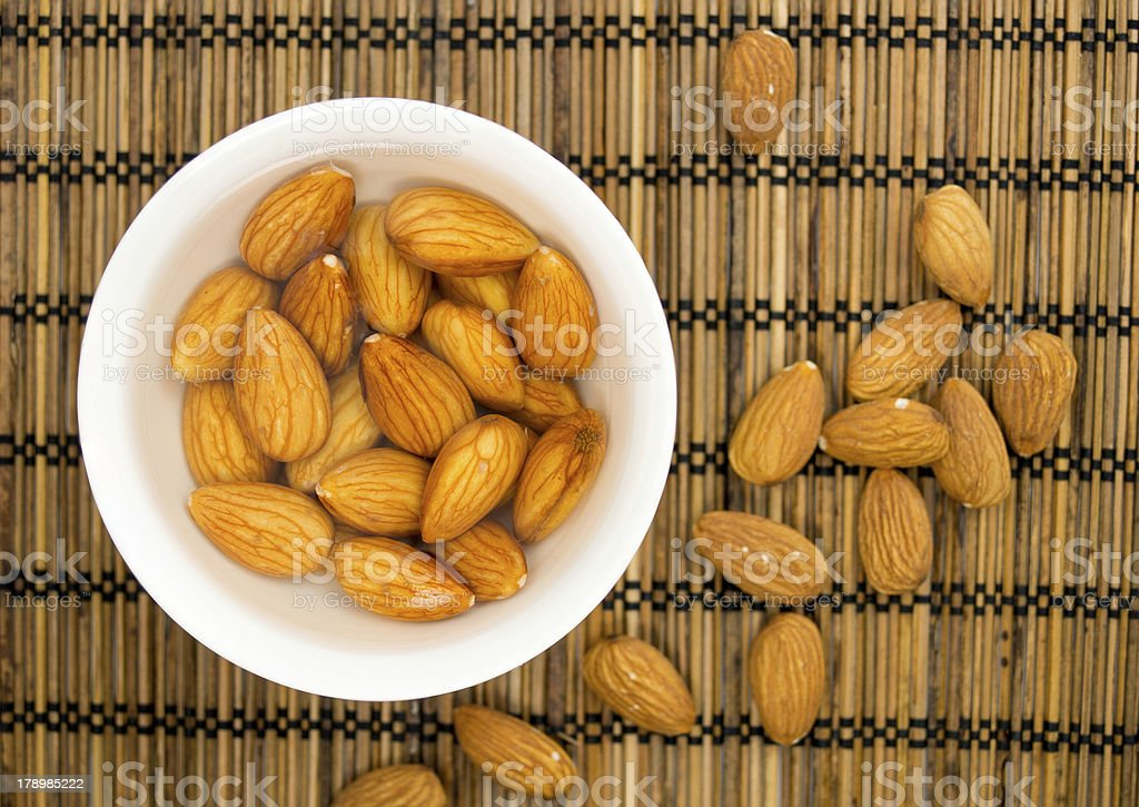 Bowl of soaked almonds against a straw mat stock photo
