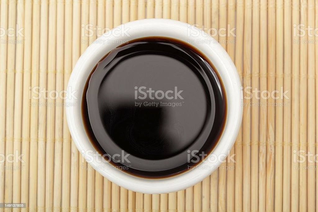 A bowl of soy sauce on a wooden mat  stock photo