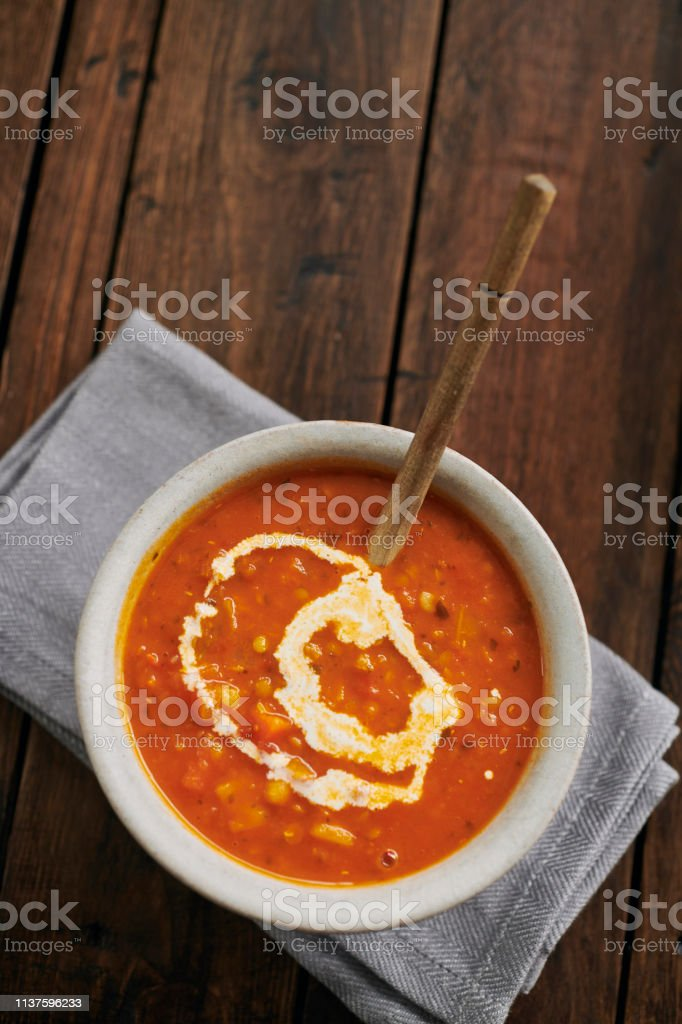 Bowl of Spicy Lentil Soup topped with a swirl of cream. stock photo