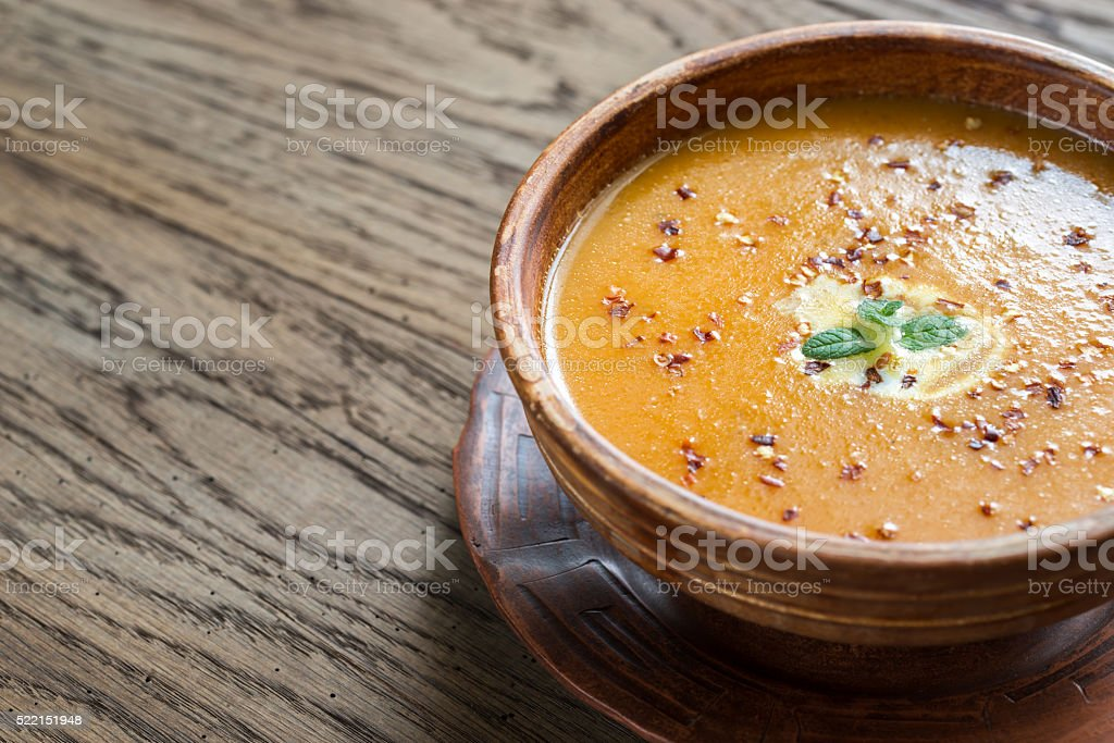 Bowl of spicy pumpkin cream soup on the wooden table stock photo