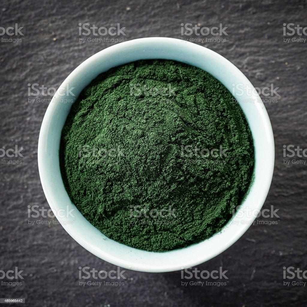 bowl of spirulina algae powder stock photo