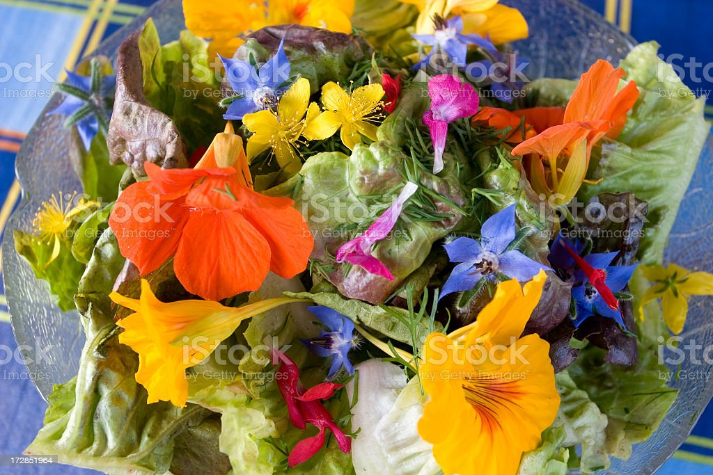 A bowl of summer salad with edible flowers stock photo