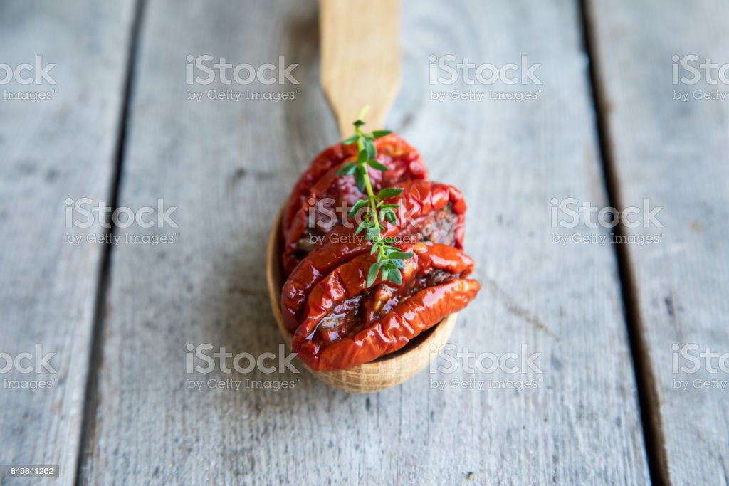 Bowl of sun dried tomatoes on wooden background. Sun dried tomatoes with olive oil and herbs stock photo