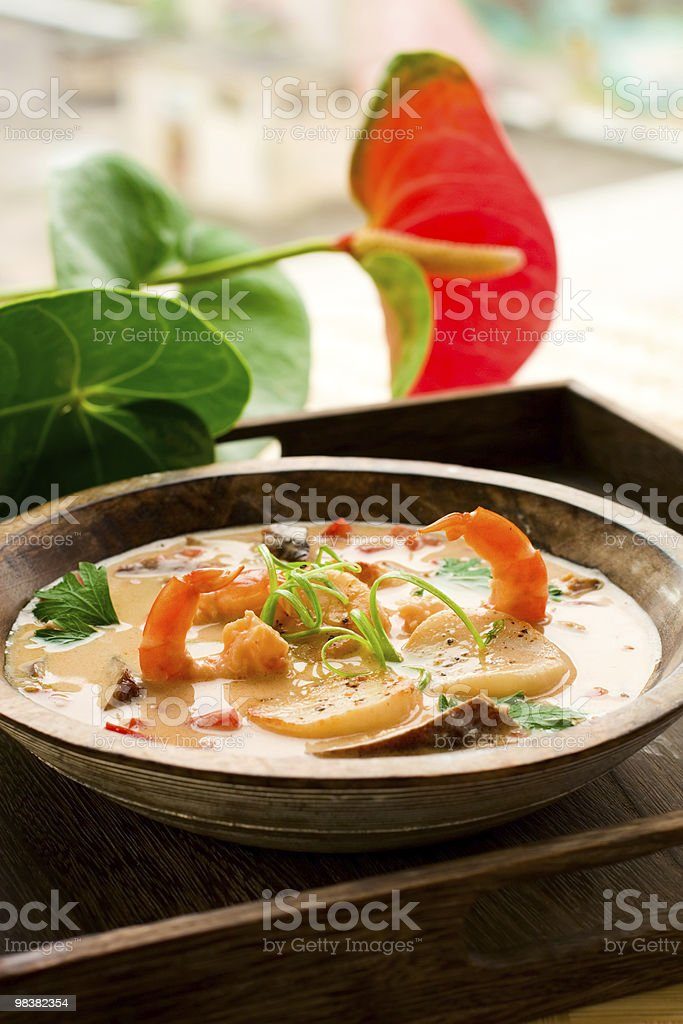 A bowl of Thai soup with prawns and scallops and garnish royalty-free stock photo